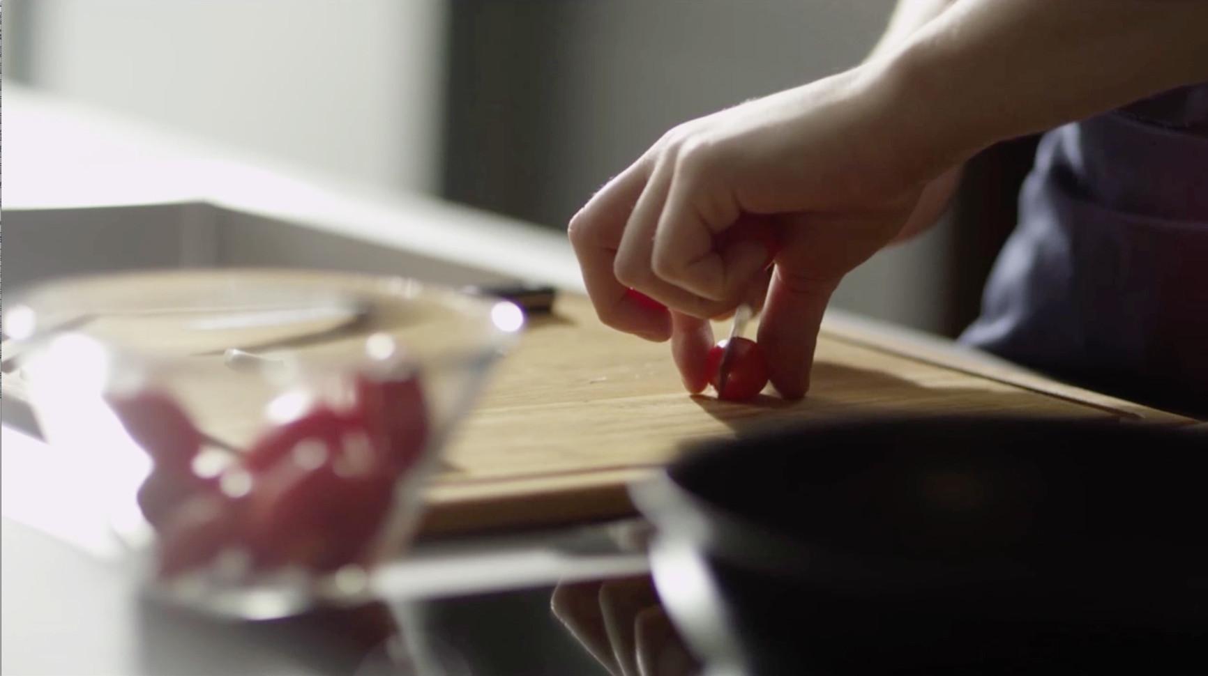 cheff taglia il pomodoro sul piano della cucina stosa
